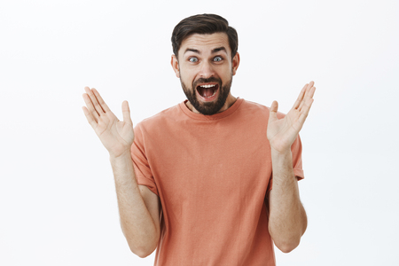 Waist-up shot of enthusiastic happy and triumphing delighted 30s male with beard widen eyes amazed and pleased clapping hands from delight and satisfaction as reacting to awesome news over gray wall Stock Photo