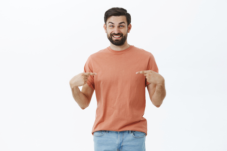 Portrait of optimistic and charismatic happy upbeat bearded guy smiling cheerful as pointing at himself with both hands as wanting be picked or chosen, showing t-shirt space