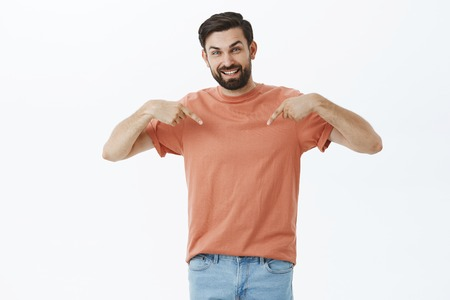 Portrait of satisfied good-looking carefree dark-haired bearded male in 30s, pointing down or t-shirt with happy and joyful smile gazing at camera showing cool product over gray background Stock Photo