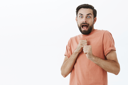 Guy screams as raising fists in defense as being scared in dark, widen eyes step back and open mouth from fright, watching too many horror movies being coward, posing in stupor over gray wall