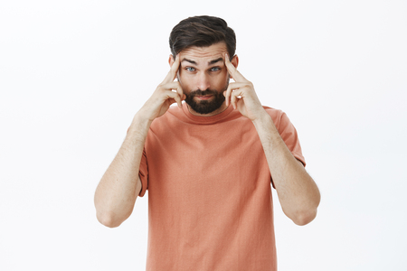Head going crazy while guy trying understand what happening. Intense frustrated and perplexed smart male entrepreneur with dark beard in pink t-shirt holding temples feeling pressure and distress Stock Photo