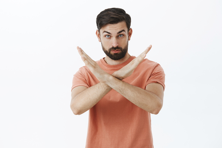 Portrait of serious and confident bearded male friend showing cross with hands making not and prohibition gesture demanding quit, forbid some action over gray background Stock Photo
