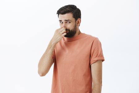 Disgusted and displeased unhappy male with beard closing nose with fingers looking at creepy and awful object which reeks with terrible smell looking at lower right corner dissatisfied