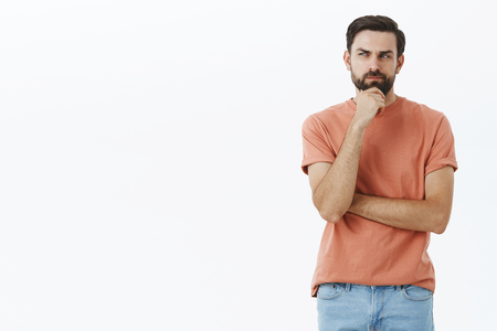 Man thinking up excuse to skip work. Smart and thoughtful creative attractive male model with beard rubbing chin squinting looking focused left while thinking making idea or plan over gray wall