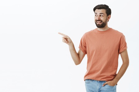 Amused and happy handsome 30s man with beard laughing and smiling, pointing and looking left inrigued of awesome interesting product asking question as willing buy it over gray background