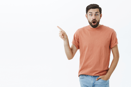 Guy shocked watching amazing show. Portrait of impressed and speechless astonished handsome 30s male with beard, drop jaw and widen eyes at camera as pointing at upper left corner excited