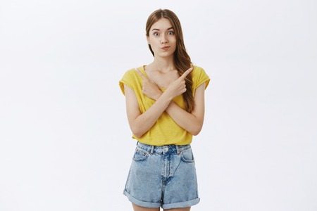 Hesitant attractive slender woman with cute braid in yellow t-shirt crossing hands against chest pointing left and right smirking cannot make choice facing decision posing against gray background