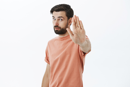 Studio shot of confident handsome adult male friend pulling palm towards camera in stop to hold drunk friend and prevent accident standing determined prohibiting or forbidding something over gray wall Stock Photo