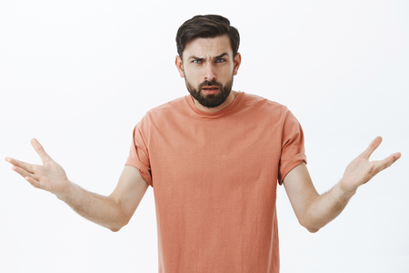 Confused and annoyed angry bearded boyfriend cannot understand why arguing, frowning with clueless emotions shrugging raising hands sideways in dismay, asking question intense and irritated