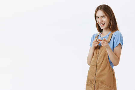 Portrait of flirty and amused charming european female girlfriend in brown overalls and blue t-shirt pointing with finger guns at camera and smiling hinting or flirting