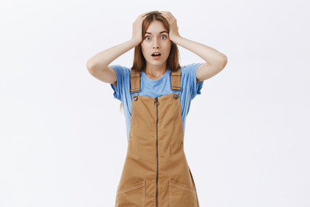 Confused and questioned troubled girlfriend in brown overalls grabbing head with both hands opening mouth and popping eyes worried at camera feeling anxious and panicking posing over grey wall