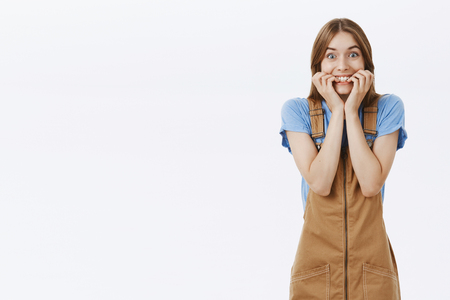 Portrait of surprised happy woman gazing with anticipation and joy biting fingernails and smiling broadly with temptation and admiration standing happy and excited against gray background