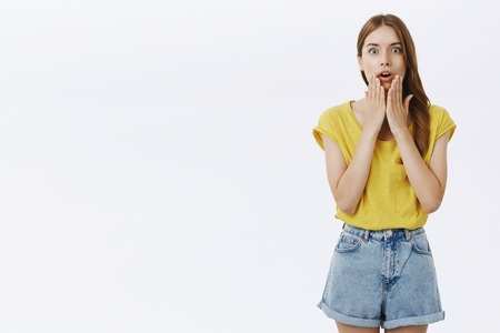 Impressed excited good-looking female meeting star looking with admiration and astonishment in casual t-shirt and shorts touching cheeks with palms opening mouth from surprise over gray background