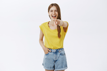 Portrait of amused cruel stylish popular girl in yellow t-shirt pulling index finger at camera and laughing out loud mocking over funny person having fun chuckling against gray background