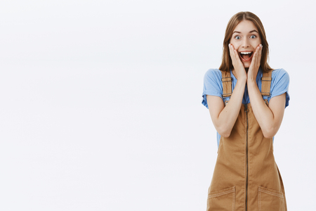 Attractive emotive girl reacting to awesome news. Portrait of impressed astonished happy girlfriend in brown trendy overalls over blue t-shirt holding palms on cheeks and smiling broadly joyfully
