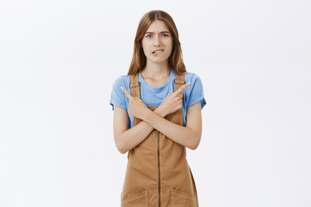 Concerned nervous cute young female student in brown overalls biting lower lip anxiously crossing hands over chest, pointing in different directions, left and right hesitating to make important choice