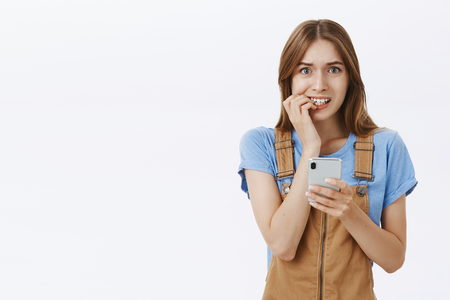 Concerned cute woman hesitating to send message inviting guy she likes on bday biting fingernails nervously holding smartphone gazing doubtful and unsure at camera over gray background Stock Photo