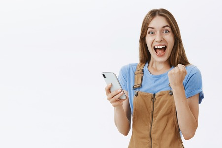 Waist-up shot of triumphing charming lucky girlfriend in brown overalls raising clenched fist in joy and victory celebrating new score in game holding smartphone hazing happy at camera over grey wall Stock Photo