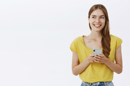 Creative cheerful and charismatic young attractive female with braid looking left with happy white smile holding smartphone expressing happiness and joy after reading cute message in cellphone