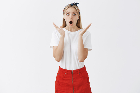 Portrait of impressed and overjoy attractive young woman with blond hair in headband and stylish clothes gesturing with palms, opening mouth in wow, being surprised and amazed by perfomance