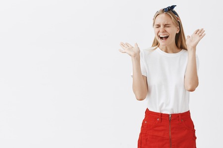 Studio shot of silly overemotive attractive and stylish girl with carefree and happy excpression waving palms near face and laughign out loud with closed eyes being very surprised and joyful Stock Photo