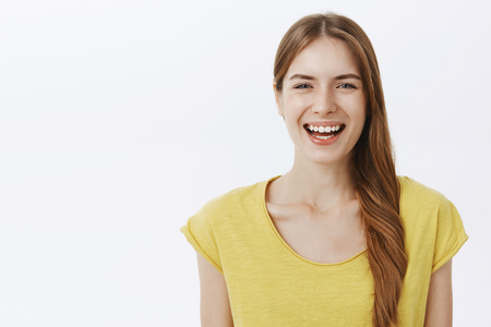 Close-up shot of kind happy charming european woman with braid in yellow birght t-shirt smiling joyfully at camera having fun enjoying nice friendly conversation standing against white background Stock Photo