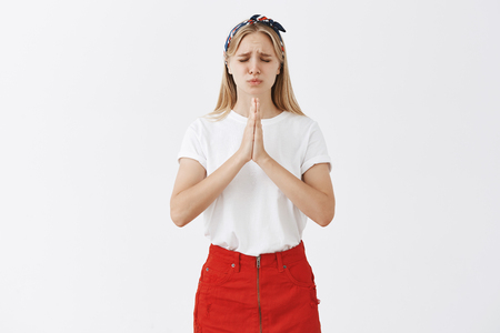 Putting all efforts in pray to make dream come true. Intense nervous attractive blonde with headband and trendy skirt, frowning, begging for help of god, closing eyes and holding hands together