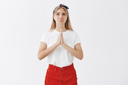 Studio shot of displeased funny european female with fair hair in headband and skirt, frowning and pursing lips while holding hands in pray on chest, looking up hopefully, begging for help of god