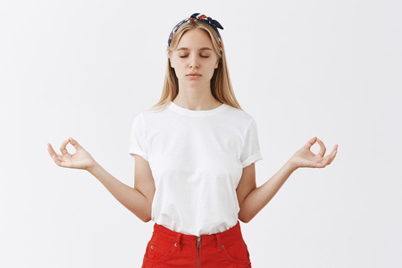 Indoor shot of focused calm and relieved attractive fair-haired woman in red skirt and headband raising hands aside with zen gesture closing eyes during meditation or yoga practice over gray wall
