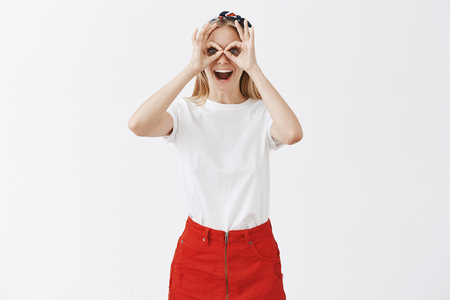 Playful immature good-looking female student with blond hair in red skirt and white shirt showing okay or zero gesture over eyes as if gazing through goggles or binocular having fun over grey wall 免版税图像