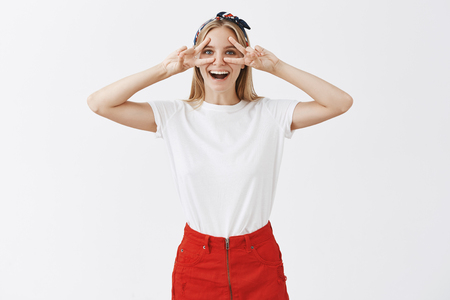 Enjoying weekends during tourist trip. Joyful good-looking european female student in stylish outfit and headband, showing victory or peace signs over eyes and smiling broadly with happy look