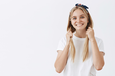 fair-haired woman in headband, pulling hair down with both hands and smiling joyfully, being in playful and joyful mood, having fun over grey wall