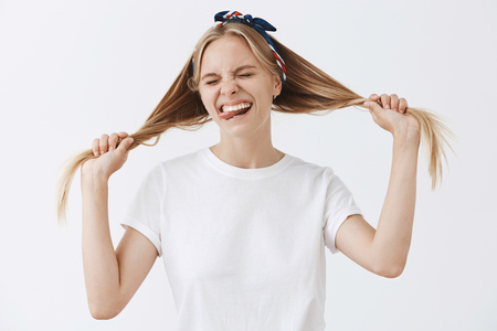 Studio shot of overjoying good-looking happy teenage girl in headband and white t-shirt pulling hair aside with hands making faces and smiling