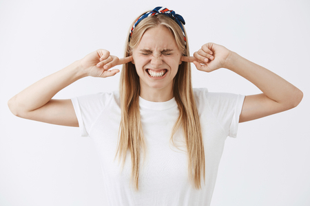 Studio shot of intense good-looking young girl with fair hair in headband grimcaing, clenching teeth closing ears and eyes ready for big bang or loud sound, standing over gray background