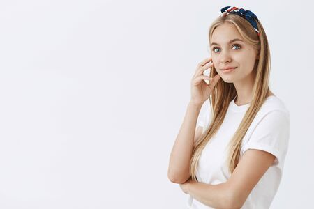 Good-looking fashionable and modern lady wearing headband, standing half-turned over grey wall, touching face and smiling Stock Photo