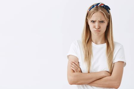 Waist-up shot of offended and moody cute female with blond hair frowning and pursing lips, looking from under forehead bothered and upset feeling insulted