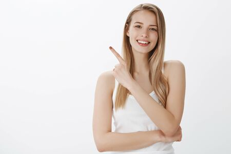 Pleasant pretty and sincere young woman with fair hair and cute moles pointing at upper left corner Stock Photo