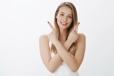 Friendly-looking carefree and relaxed young attractive woman with blond hair crossing hands across body to pointing sideways as smiling joyfully presenting products left and right