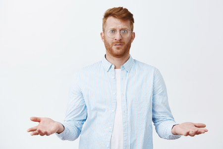 Confused gloomy handsome redhead guy with beard in glasses and shirt, standing with questioned expression and spread palms in clueless pose, being unaware and unsure what happened 写真素材