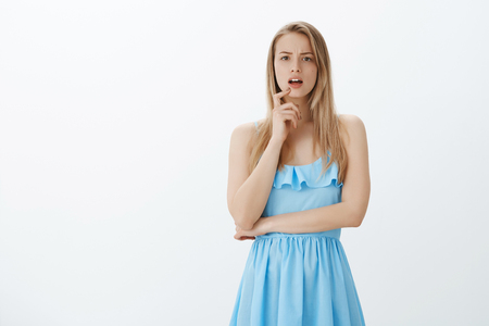 Girl starting realize what happening having idea, standing with opened mouth as frowning and touching lip with finger, thinking, being unsure and confused posing in cute blue dress over gray wall Stock Photo
