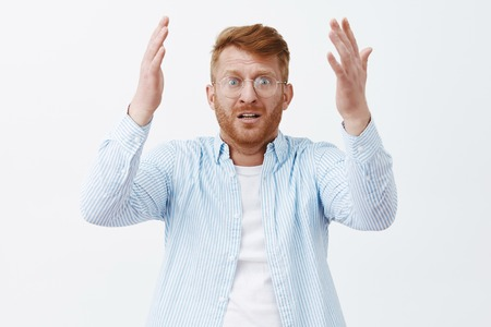 Desperate upset guy looking at his favorite player making huge mistake, feeling disappointed and shocked, standing worred over gray wall with raised hands and nervous expression in glasses and shirt