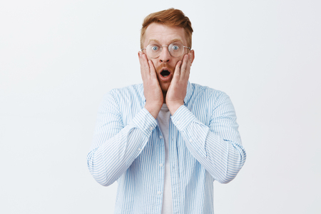 Man being shocked witnessing terrible scene. Portrait of stunned terrified redhead male in glasses and shirts dropping jaw, gasping from amazement, staring at camera worried over gray background Stock Photo