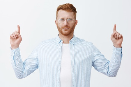 Good-looking serious and smart businessman with red hair in glasses and shirt, lifting index fingers to point upwards, standing over grey wall calm