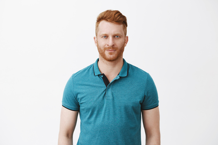 Waist-up shot of attractive masculine macho man with ginger hair in green polo shirt smirking and gazing with confident and self-assured expression at camera, feeling calm and ready to work