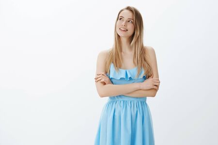 Attractive cute blonde girl in stylish blue dress fantasizing what presents she will get at birthday party