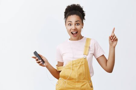 Why standing let us dance. Good-looking feminine trendy woman with dark skin and curly hair in stylish yellow overalls, moving in rhythm of music, holding smartphone and listening songs in earphones Foto de archivo