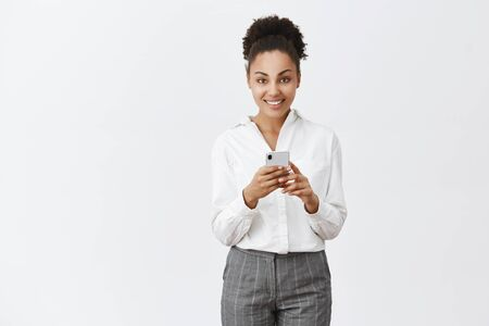 Good-looking businesswoman with dark skin in suit, holding smartphone and gazing at camera with broad smile, talking with client via messages, waiting for coffee in cafe on way to office in morning Archivio Fotografico - 133551004
