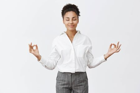 Stress free, only peace inside. Charming relaxed and carefree female in bossy outfit, raising hands in zen gesture, smiling with closed eyes while meditating or practicing yoga, feeling relieved Reklamní fotografie