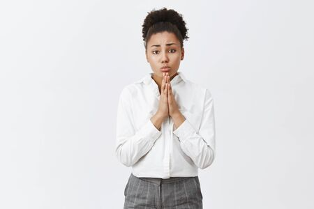 Begging you for mercy. Portrait of upset cute african-american in white shirt and pants, holding hands in pray near chest, pursing lips and frowning while askking apology or help over gray background Stok Fotoğraf