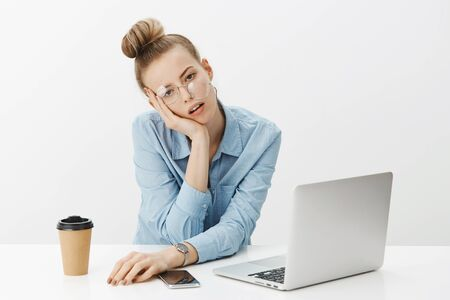 Girl falling asleep on work, feeling tired overworking late night leaning head on palm as glasses falling from face, open mouth and staring bored and sleepy at camera, drinking coffee over gray wall